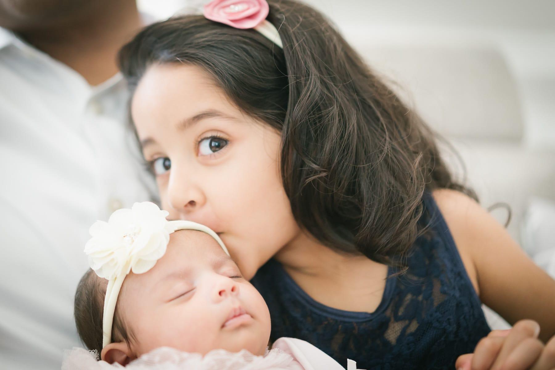 Familienfotograf Lörrach Freiburg Mäschen küsst Baby